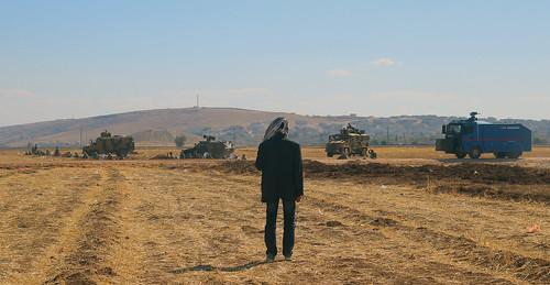 Un manifestante kurdo observa a las fuerzas de seguridad turcas en el paso fronterizo de Mursitpinar
