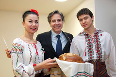 Deputy Secretary of State Antony 'Tony' Blinken is welcomed to the Embassy Chisinau community with the offering of traditional Moldovan bread and salt, and a martisor, the red and white string from which a small decoration is tied that is offered by people on the first day of March, during his trip to the capital city on March 3, 2015. [State Department photo/ Public Domain]