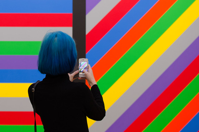 A visitor captures a double rainbow at Wall Drawing #1084 by Sol Lewitt at Amsterdam's Stedelijk Museum.