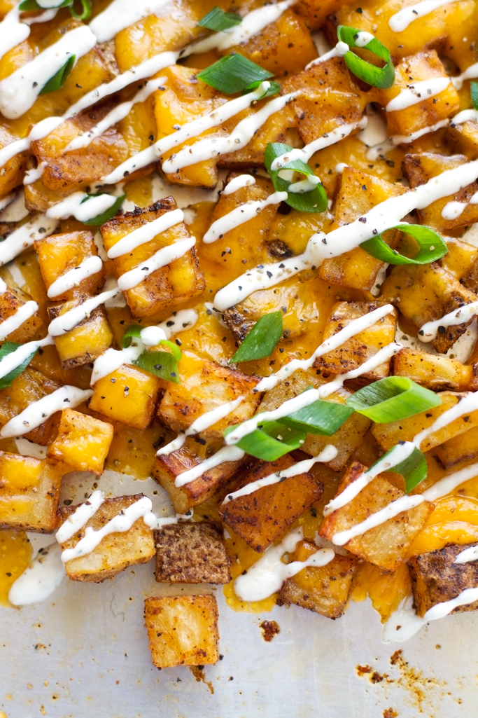 Cheesy Ranch Roasted Potatoes - Baked southwestern potato bites topped with a ranch greek yogurt sauce! #potatobites #potatowedges #vegetarian #greekyogurtsauce #ranchdressing | littlespicejar.com