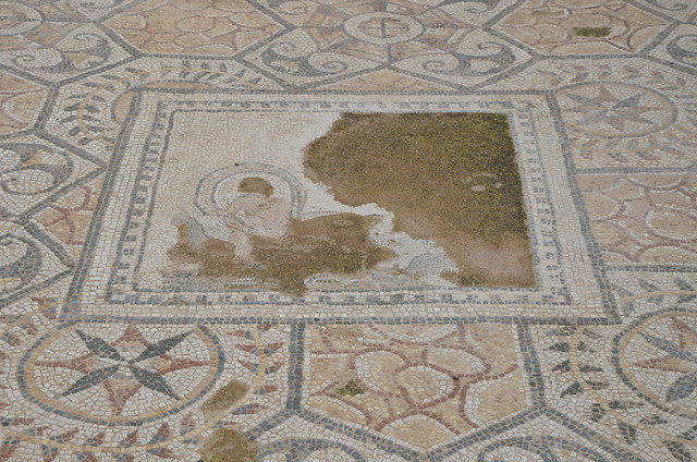 Mosaic floor from one of the cubicula of a patrician house in black, white and ochre with an emblema depicting a nymph riding a dolphin, Nora, Sardinia