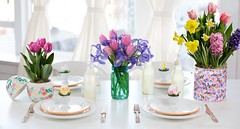 flower pot decoration including hyacinth narcissus crocus Wirosa tulips on table with settings plates silverware