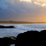 Big white waves roll in to Godrevy near Gwithian in St Ives Bay Cornwall just after a storm in sunset.