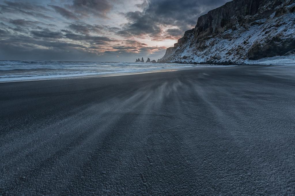 Sunset on a stormy black beach