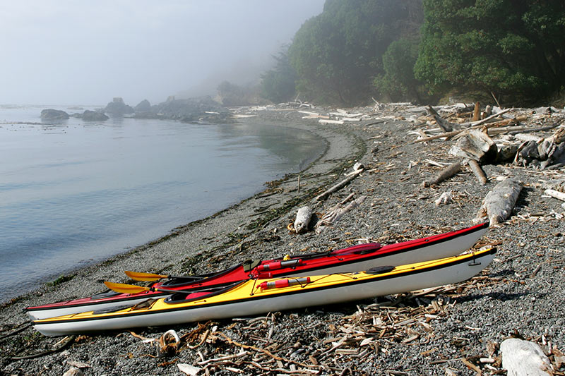 Sea kayaks on a remote beach on Vancouver Island, British Columbia, Canada.