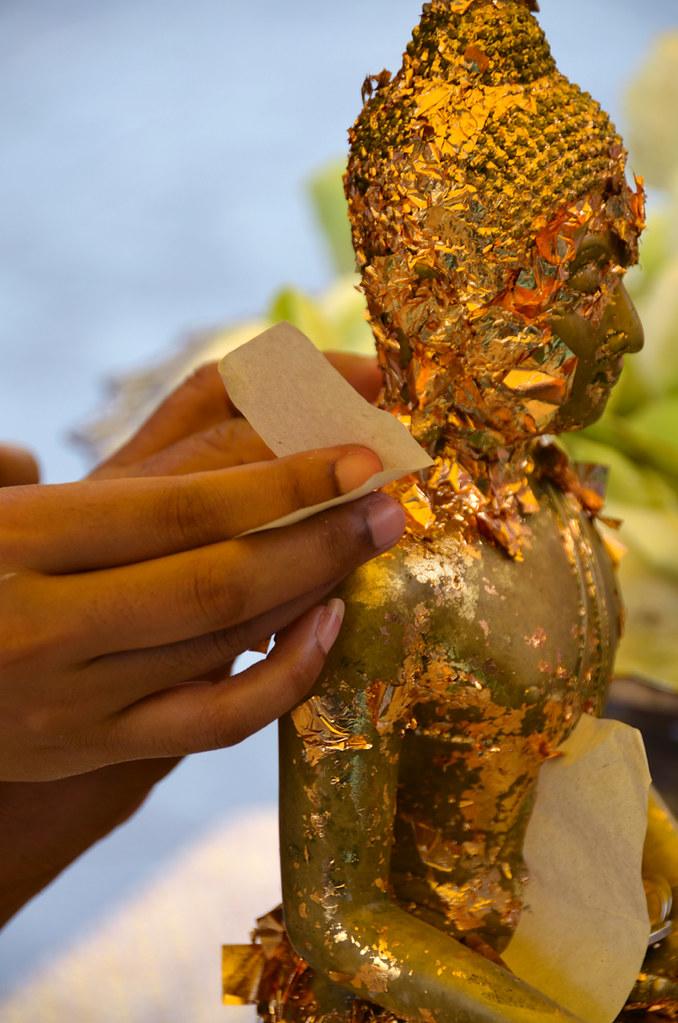 Colocando pan de oro a un buda de Tailandia