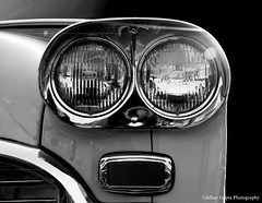 wheel(0.0), rim(0.0), bumper(0.0), automobile(1.0), automotive exterior(1.0), vehicle(1.0), automotive lighting(1.0), automotive design(1.0), light(1.0), monochrome photography(1.0), grille(1.0), headlamp(1.0), land vehicle(1.0), monochrome(1.0), black-and-white(1.0),