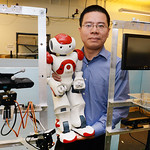 Dr. Weihua Sheng holds a robot in his lab where he is researching social intelligence for robots being developed at OSU to assist the elderly. To his right and left are current prototypes of robots equipped with cameras and audio sensors to monitor the health and needs of people needing assistance with daily living. The project includes improving the functionality of the prototypes and adding features to make them appear more human.