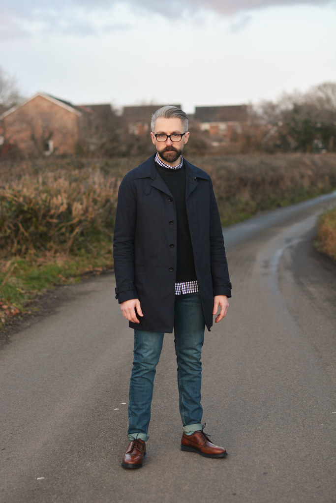 Menswear: Smart navy raincoat, crew neck knit, gingham shirt, jeans and brogues