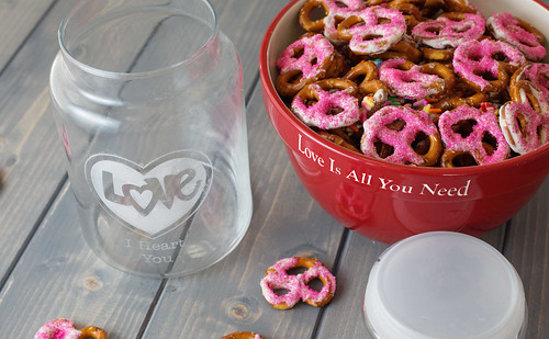 pink Valentine's Day yogurt coated pretzels in a bowl with glass mason jar on wood table