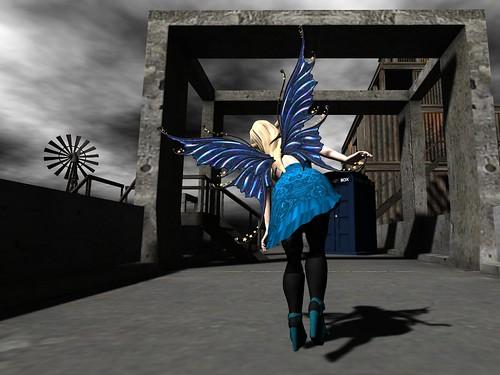 Image Description: Woman in a blue dress hopping down a stone bridge toward a TARDIS.