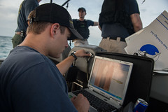 Navy Diver 2nd Class Daniel Soulliard monitors the readings from a Tow Fish side scan sonar system during operations in the Java Sea. (U.S. Navy/MC2 Antonio P. Turretto Ramos)