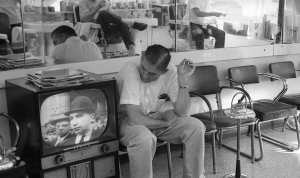 Man watching television news inside barbershop in Tallahassee.