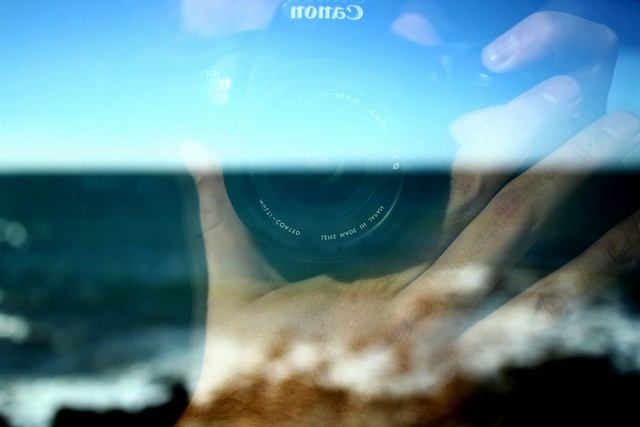 Self portrait with the mediterranean sea as background against a moving train window