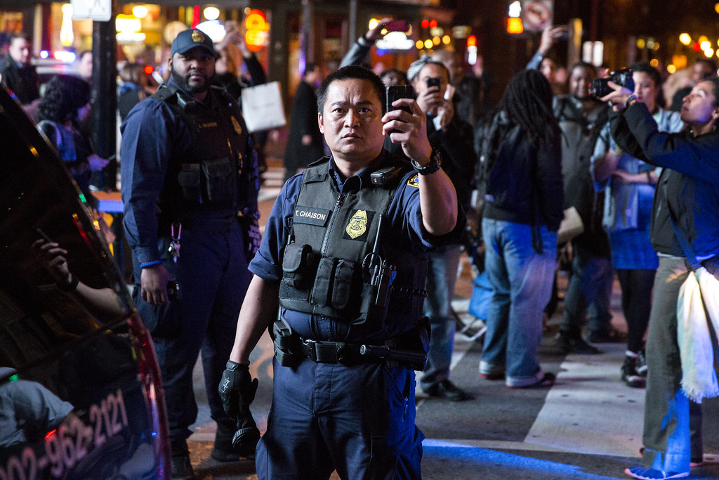 a police officer filming a crowd of protesters