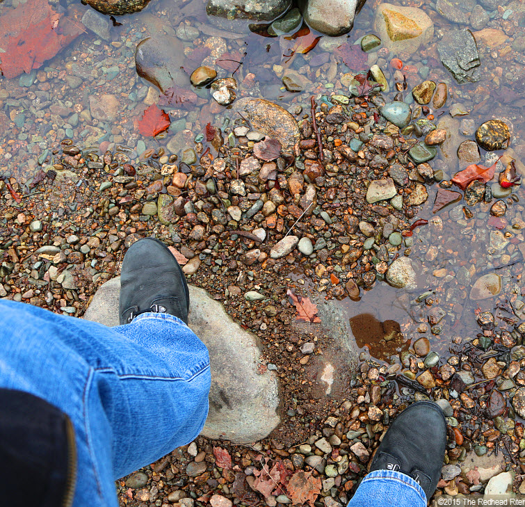 standing in river on rocks with black Timberland boots