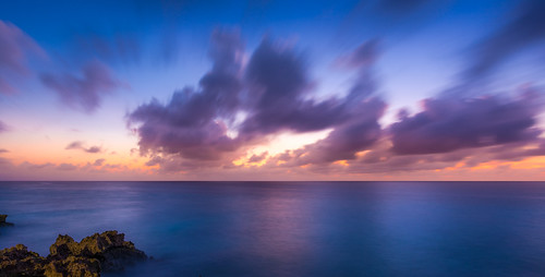 ocean sunset sky orange water rock clouds sunrise moving still long exposure smooth magenta grand cayman bluecolor