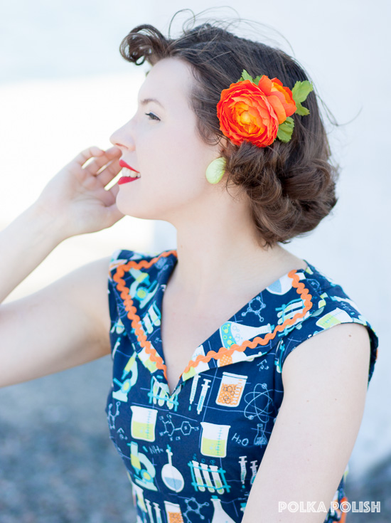 Bright orange hair flower and chartreuse green earrings bring out bold colors in a retro science novelty print dress