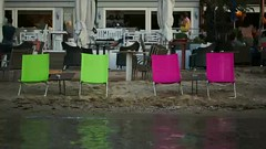 Empty chaise-lounges on the beach and outdoor cafe