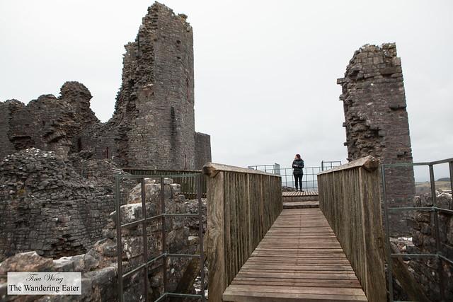 Walking the wooden bridge to access Carreg Cennen Castle