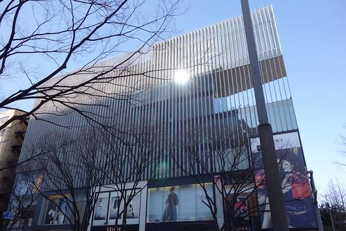 """Shibuya_5 表参道のビルディングを撮影した写真。 """"ONE 表参道"""" である。 建物前面の壁面に等間隔に垂直に細長い板が襞の様に並んでいる。 落葉した並木が写真に写っている。"""