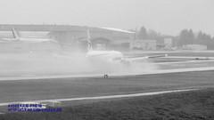 BLACK & WHITE OF 777-300ER KICKING UP WATER ON WET PAINE FIELD RUNWAY