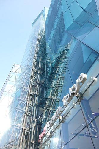 "Shibuya_29 渋谷の明治通りに面した所にある高層ビルディングを撮影した写真。 右の ""THE ICEBERG ビルディング"" の前面はターコイズブルー色のガラス張りで複雑な三次元ジオメトリック構造をしている。 エレベーターのワイヤーやフレーム構造がガラス面に映り込んでいる。 左の ""THE ICEBERG ビルディング"" は前面が数多の三角形のガラス張りである。"