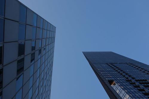 """Shinjuku_5 新宿で撮影した高層ビルディングの写真。 右は """"セントラルパークタワー・ラ・トゥール新宿""""。 日が暮れ始めやや薄暗くなっている。 地上からほぼ直上を見上げるようにして撮影したもの。 右側のビルディングの角は際立った鋭角である。"""