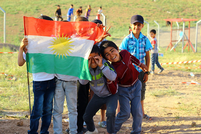 Refugiados sirios portan la bandera del Kurdistán en el campo de refugiados de Akre