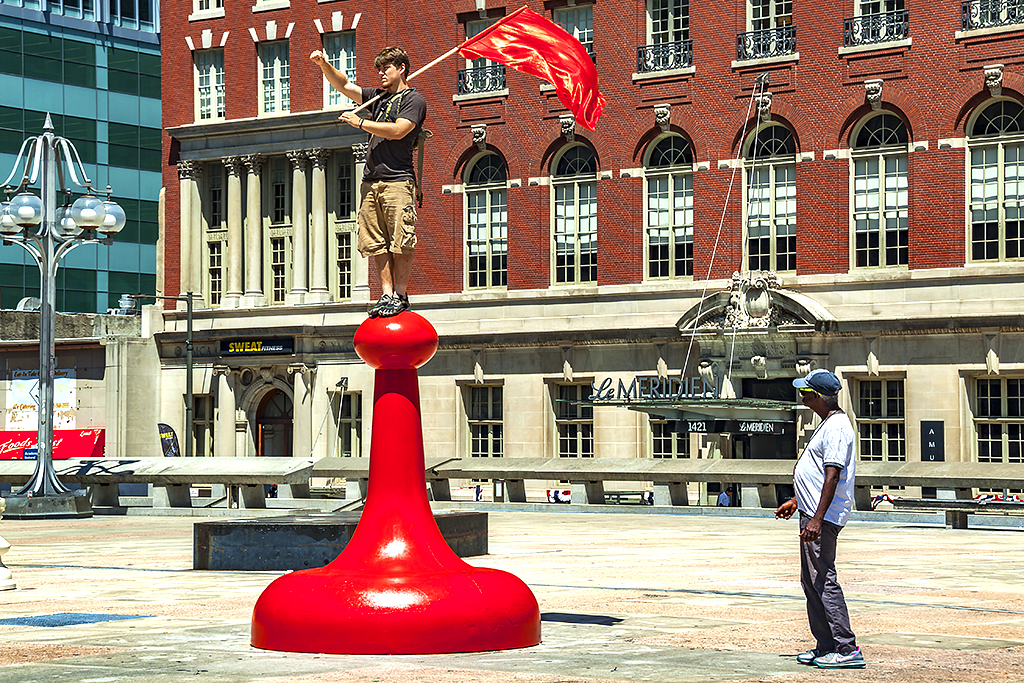 Young man with red flag standing on red pawn--Center City