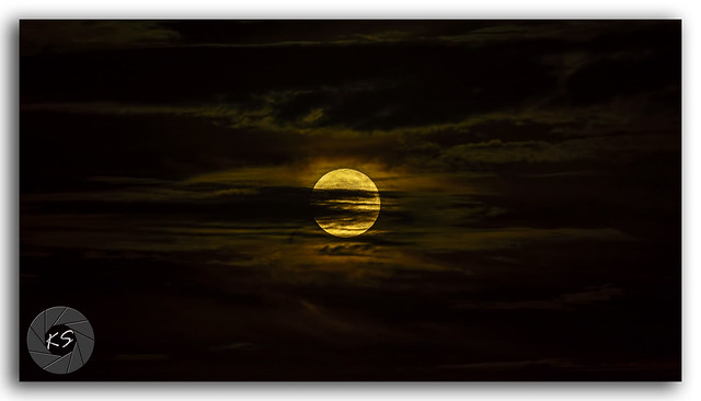 Full moon surrounded by silky clouds at night