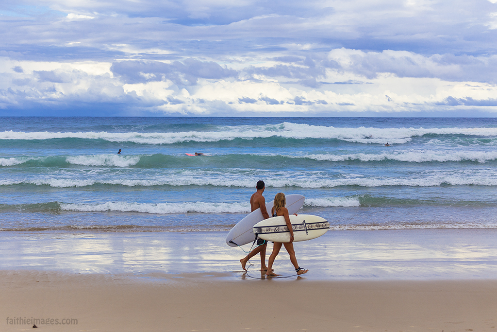 Couple walking on the beach carrying surfboards
