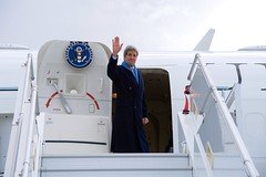 U.S. Secretary of State John Kerry waves goodbye at Geneva International Airport as he departs Geneva, Switzerland, on March 4, 2015, following his latest round of negotiations with Iranian officials about the future of their nuclear program. [State Department photo/ Public Domain]