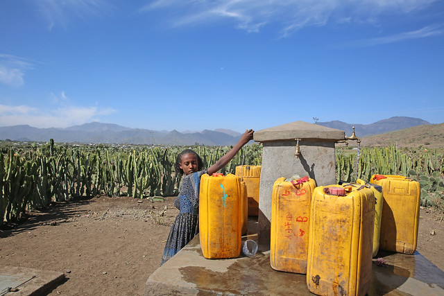 Young girl fetchs water from a new water point built by the support of UNICEF