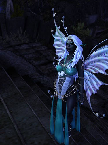 Image Description: Drow in a revealing teal and gold outfit walking up a set of stairs.