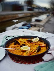 Seafood paella with glass of wine in seaside cafe,…