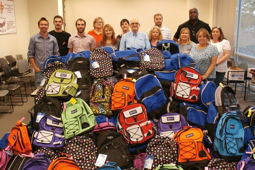 Photo of DTP employees with donated backpacks