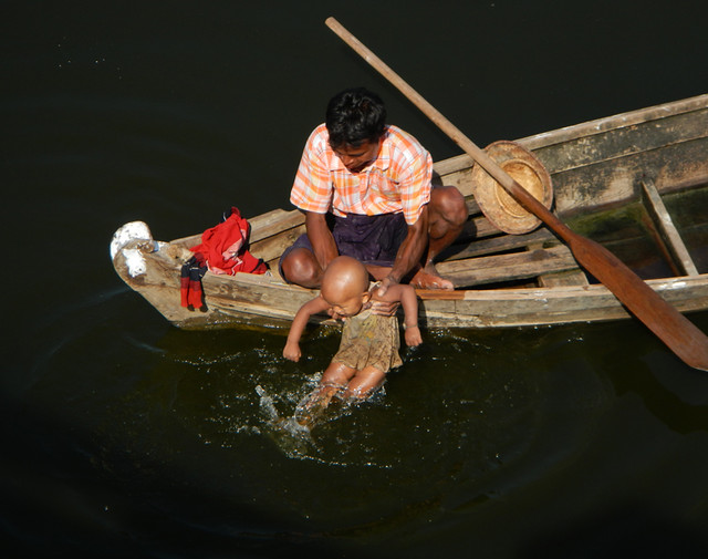 Washing the baby from a boat by the U Bein Bridge in Mandalay, Myanmar