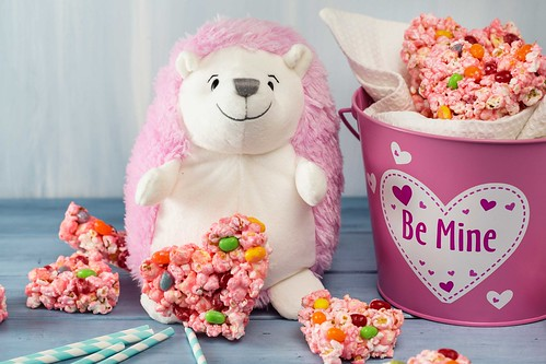 pink stuffed animal hedgehog with popcorn and jelly bean marshmallow treats and a pink bucket with Be Mine on it for Valentine's Day