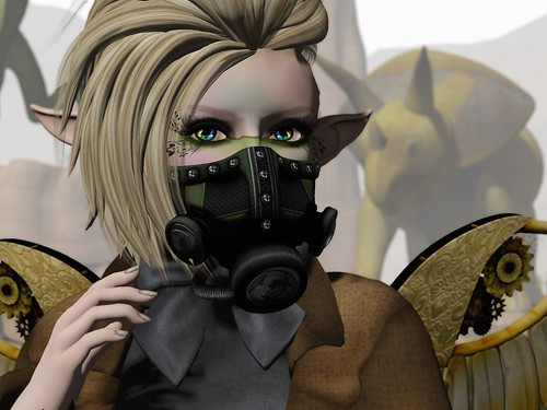Image Description: Close up of a woman's face over a gas mask; she has spiky hair, shaved on one side.