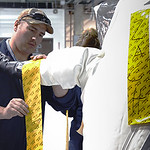 Pueblo Chemical Agent-Destruction Pilot Plant ordnance technicians prepare for a practice demilitarization protective ensemble entry inside the Enhanced Reconfiguration Building. The yellow tape helps seal areas of the suit where exposure to the outside environment could occur.