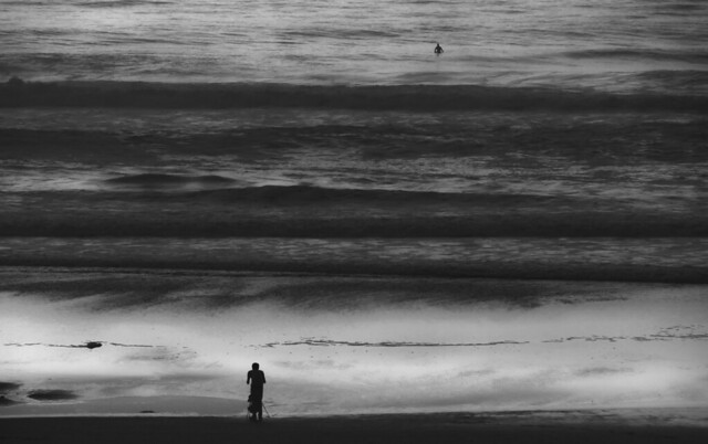 Photographer and surfer on Ocean Beach, San Francisco at dusk; February 2, 2015