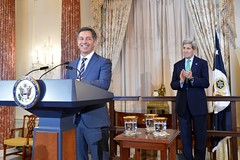 With U.S. Secretary of State John Kerry looking on, Randy Berry, the first-ever Special Envoy for the Human Rights of LGBT Persons, delivers remarks at a welcome reception in Special Envoy Berry's honor at the U.S. Department of State in Washington, D.C., on February 28, 2015. [State Department photo/ Public Domain]