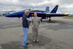 U.S. Air Force Colonel George 'Dutch' Dietrich speaks to U.S. Secretary of State John Kerry about the F/A-18 fighter jets used by the Blue Angels, the U.S. Navy's flight demonstration team, as the Secretary stopped at Joint Base Elmendorf-Richardson on July 27, 2016, for an aircraft re-fueling while the team was in town to perform at the upcoming Arctic Thunder air show. [State Department Photo/ Public Domain]
