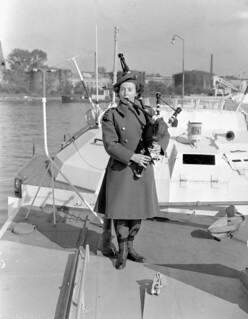 Piper Flossie Ross of the CWAC Pipe Band on the deck of a E boat, Wilhelmshaven, Germany / La cornemuseuse Flossie Ross, du corps de cornemuses du SFAC, sur le pont d'un E-boat à Wilhelmshaven, en Allemagne
