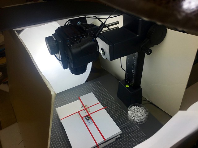 Pinned insect specimen digitization set up. A camera facing down at a platform. On the platform rests the specimen information and the pinned specimen itself. The area is surrounded with white panels and lit with muted light fixtures