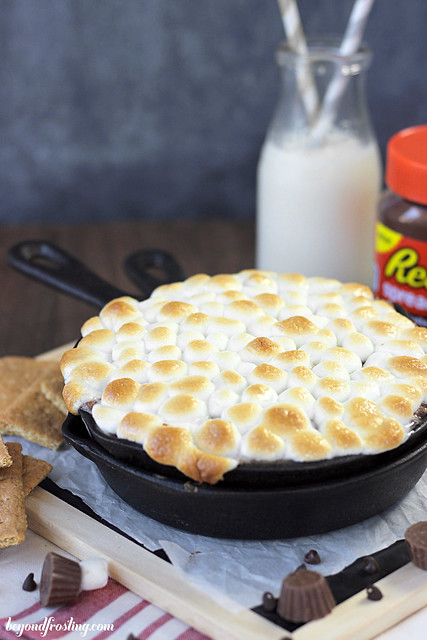 Ooey Gooey Reese's Cookie Dough S'mores Dip. The bottom layer is graham crackers, then it is topped with a peanut butter and chocolate cookie dough. This dessert dip is topped with toasted marshmallows.