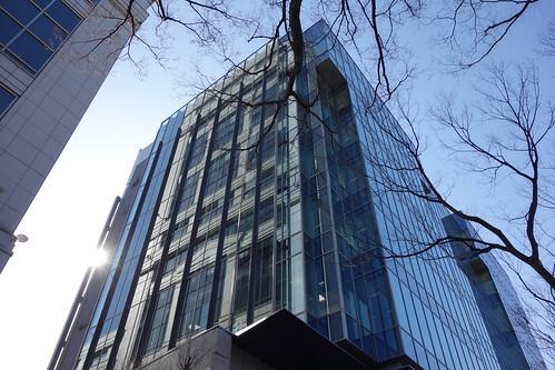 """Shibuya_6 表参道のビルディングを撮影した写真。 """"oak omotesando"""" である。 斜め下方から見上げる角度で撮影したもの。 全面ガラス張りで隣の建物が映り込んでいる。 落葉した並木が写真に写っている。"""