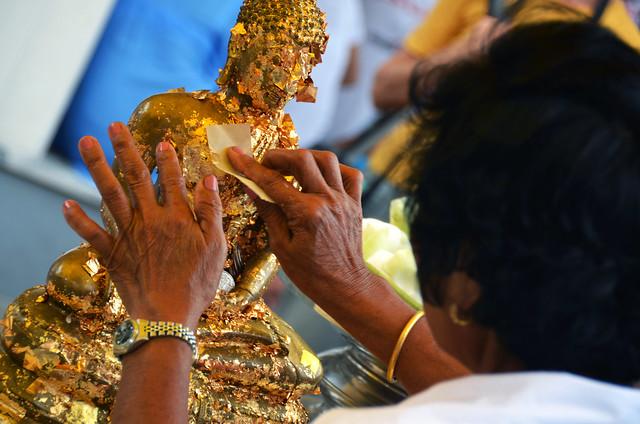 Colocando pan de oro a un buda de un templo de Tailandia