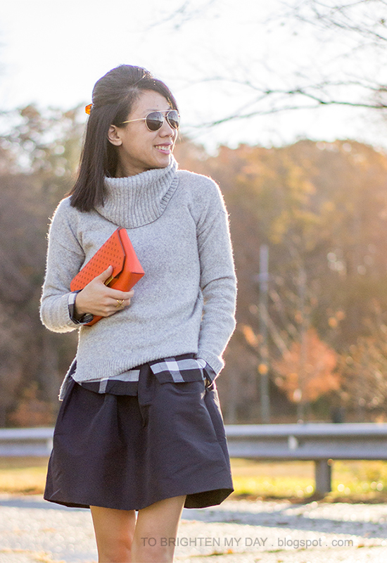 gray cowlneck sweater, navy plaid shirt, navy full skirt, orange clutch